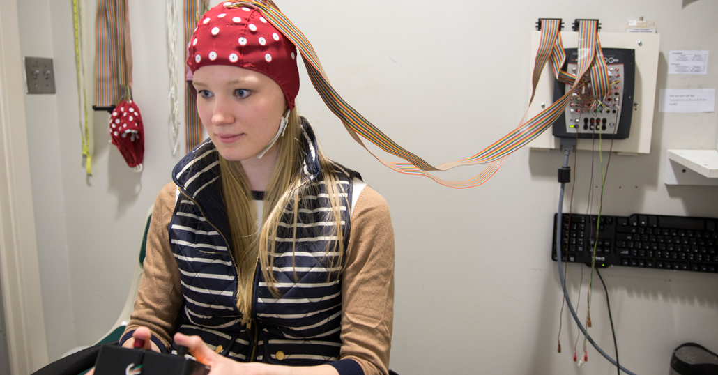a young woman wearing an EEG cap plays a video game