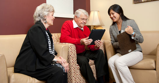 a male-female elderly couple talks with a clinic staff member