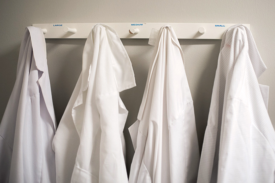 four white lab coats hanging on pegs
