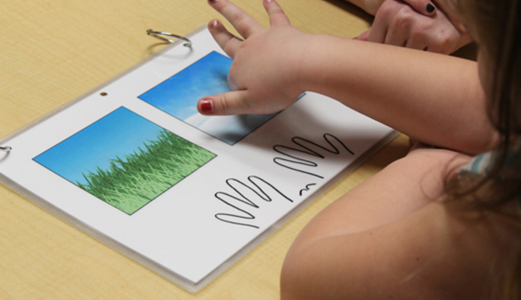 child pointing to a picture chart