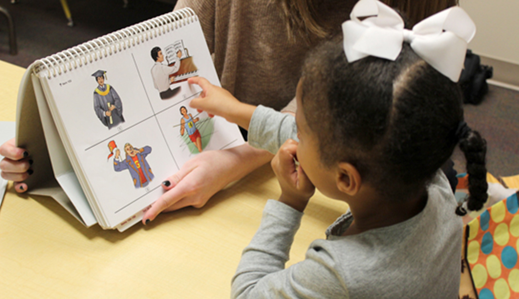child looking at a picture chart