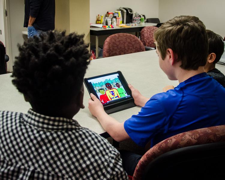 three boys playing a game on an iPad